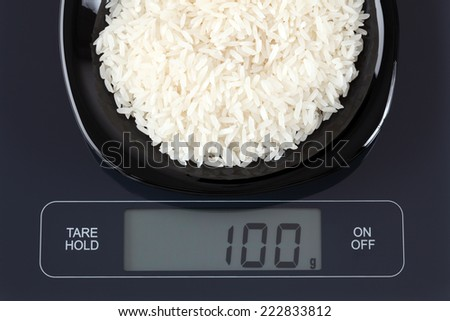 White rice in a black plate on digital scale displaying 100 gram. - stock photo