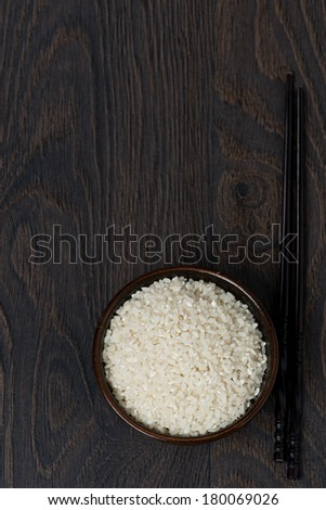 white rice in a bowl and chopsticks on dark background, top view, vertical - stock photo