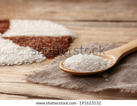 white rice in a wooden spoon on the sackcloth on an old wooden table - stock photo