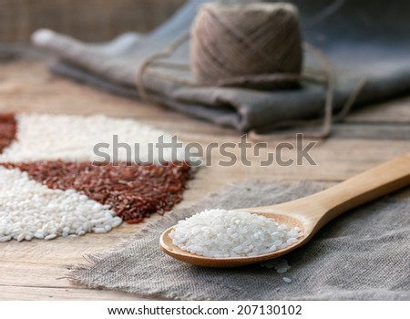white rice in a wooden spoon on the sackcloth with ball of twine on an old wooden table - stock photo