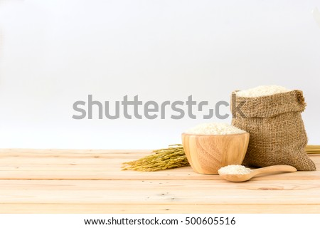 White rice in bowl and a bag, a wooden spoon and rice plant on a wooden table, Isolated in a white background, Side view with copy space
