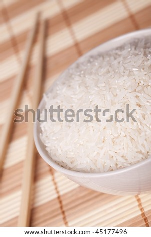 white rice in bowl and chopsticks