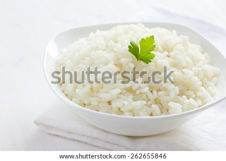 White rice in bowl on white background, selective focus - stock photo