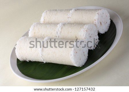 White rice Puttu.a South Indian and Sri Lankan breakfast dish of steamed cylinders of ground rice layered with coconut. Puttu is served with side dishes such as palm sugar or chickpea curry or banana.
