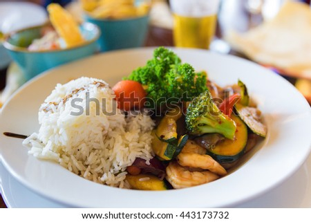 White rice with scampis and vegetables served in a soy sauce with side dishes - stock photo