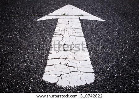 White road arrow on dark asphalt - stock photo