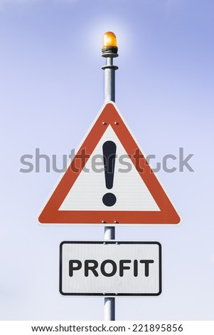 White road triangle with a black exclamation point and a red frame on a metal mast with a orange warning light on top in front of a blue sky. A second rectangular sign warns in english about Profit - stock photo