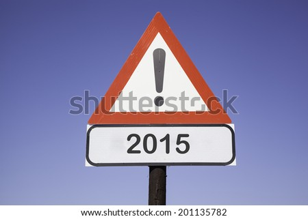White road warning triangle with black  exclamation point and red frame on  a wooden mast in front of a blue sky. A second rectangular sign warns in english about 2015