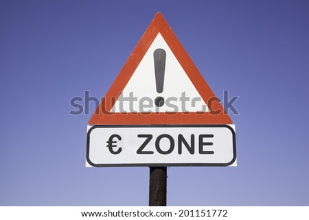 White road warning triangle with black  exclamation point and red frame on  a wooden mast in front of a blue sky. A second rectangular sign warns in english about Eurozone
