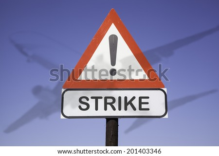 White road warning triangle with black  exclamation point and red frame on  a wooden mast in front of a blue sky. A second rectangular sign warns in english about airline strike - stock photo
