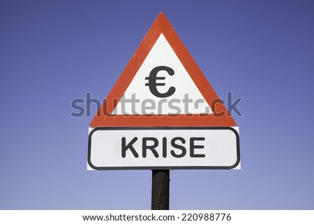 White road warning triangle with black  exclamation point and red frame on  a wooden mast in front of a blue sky. A second rectangular sign warns in german about  Euro crisis - stock photo