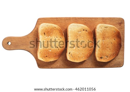White roasted bread on cutting board isolated on white background, top view