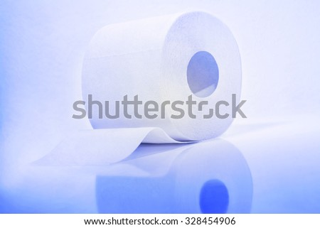 White roll of toilet paper in a blue tone. - stock photo