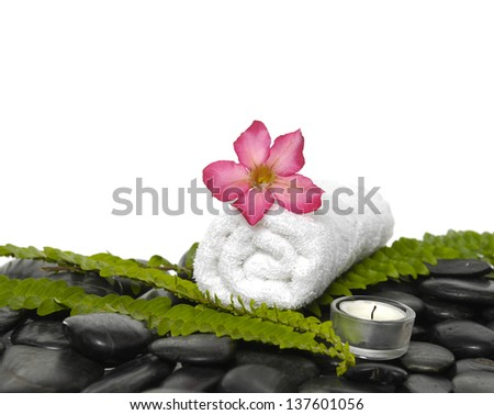 White roller towel with green fern and frangipani,candle on pebbles  - stock photo