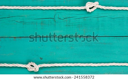 White rope with knots on blank antique teal blue rustic wooden background - stock photo