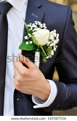 white rose boutonniere on suit of the groom - stock photo