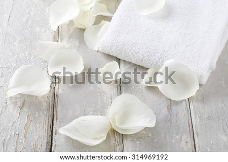 White rose petals and soft towel on a rustic wooden background - stock photo