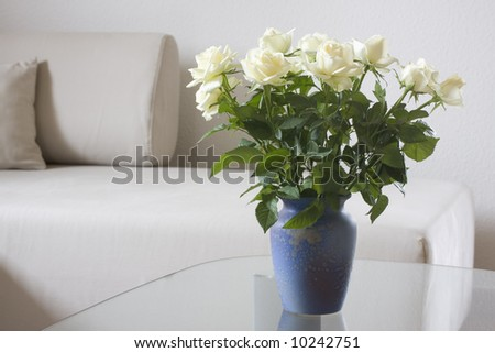 White roses on a table of glass in bright living room - stock photo