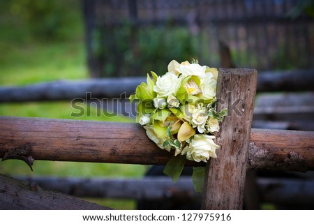 White roses wedding bouquet on rustic country fence - stock photo