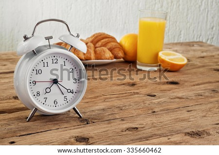 White round alarm clock on a wooden table in the kitchen with croissants and orange juice. Copy space. Free space for text or object - stock photo