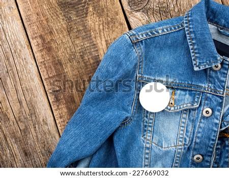 White round badge button on denim jacket - stock photo