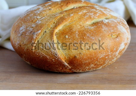 White, round bread on a wooden board. Selective focus. - stock photo