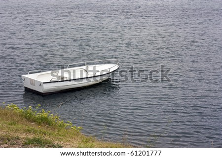White rowboat anchored near meadow in adriatic - stock photo