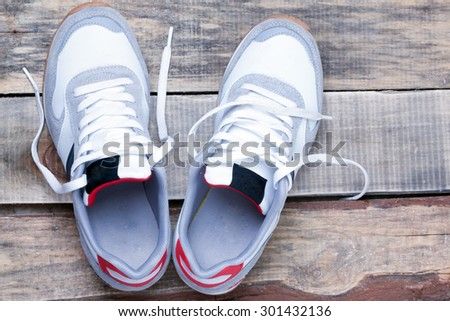 white running shoes on a wooden floor closeup view from above. - stock photo