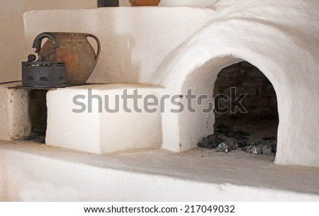 White rustic brick oven with pot and iron - stock photo