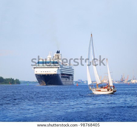 white sail yacht against large black cruise liner ship in port of Riga