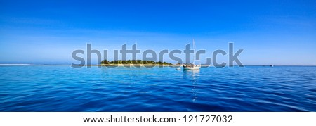 White sailing yacht in front of beautiful Fiji atoll island with white beach in the middle of the ocean. - stock photo