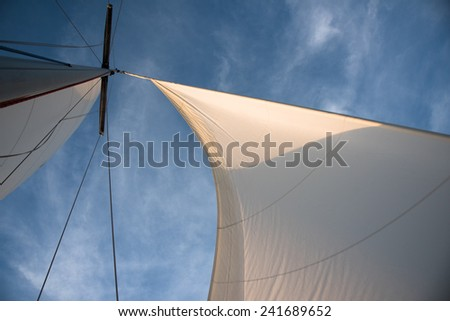 White sails and mast against blue sky with some clouds on the windful day - stock photo