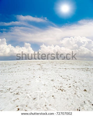 white salt desert under blue sky with clouds - stock photo