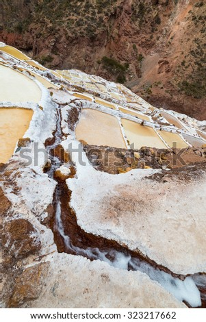 "White salt pans also known as ""Salineras de Maras"", among the most scenic travel destination in Cusco Region, Peru. Wide angle oblique view from above with flowing water in the foreground. - stock photo"
