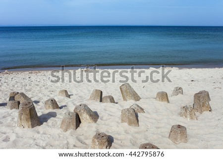 White sand Baltic Sea beach with concrete breakwater blocks at Hel Peninsula in Poland, view towards Puck Bay - stock photo