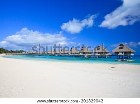 White sand beach and overwater villas in blue tropical lagoon, Bora Bora, French Polynesia, South Pacific  - stock photo