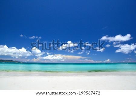 White sand beach under blue sky - stock photo