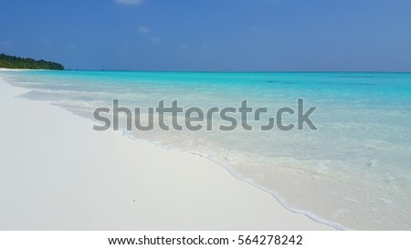 White sand beach with blue turquoise sea water with blue sky background