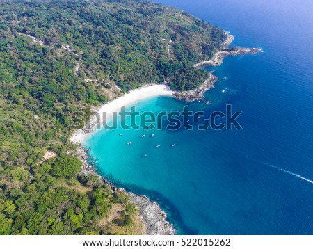 White sand beach with turquoise clear water, longtail boats, granite stones and lush tropical greenery. Top view. Aerial shooting of Freedom beach, Phuket, Thailand.