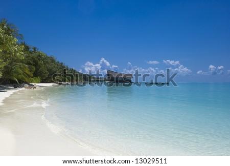 White sand beaches and crystal clear blue waters of Kuramathi island resort, Maldives - stock photo