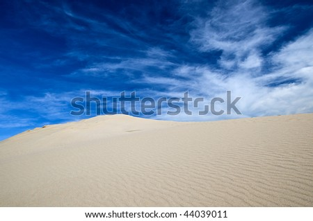 white sand dune with blue sky