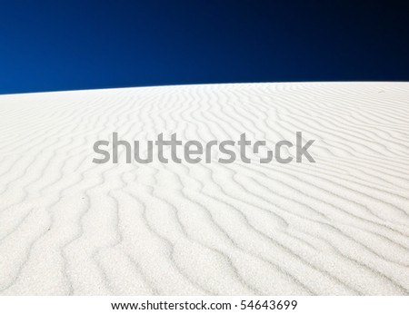 White sand dune with wind patterns and bright blue sky - stock photo
