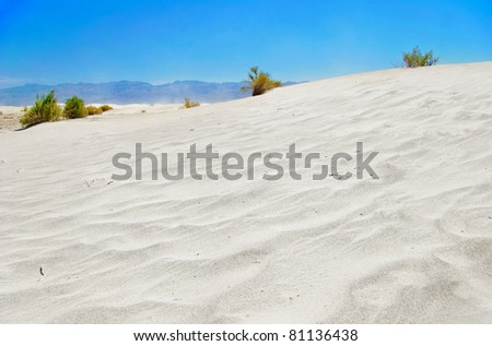 White sand dunes under blue sky, Death Valley, California - stock photo