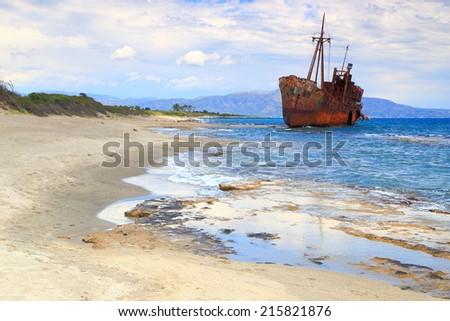 White sandy beach and sea waves with distant ship wreck near Gythio, Greece - stock photo