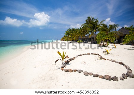 white sandy beach and turquoise water and heart made by coconut