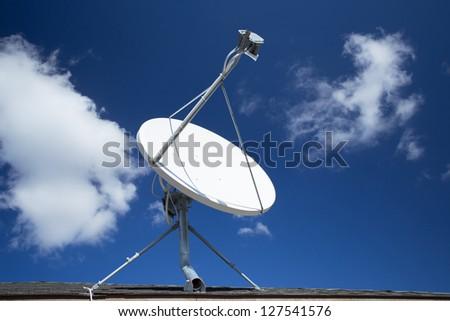 White satellite dish with blue sky - stock photo