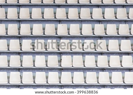 White seats on the tribune of the soccer stadium. - stock photo