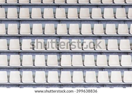 White seats on the tribune of the soccer stadium. - stock photo