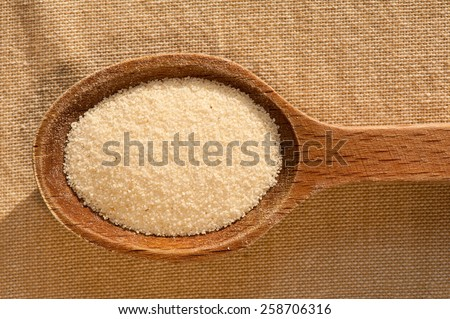 White semolina grains groats portion on wooden spoon closeup lying on table cloth, coarsely grains healthy raw food heap in day light, horizontal orientation, nobody. - stock photo