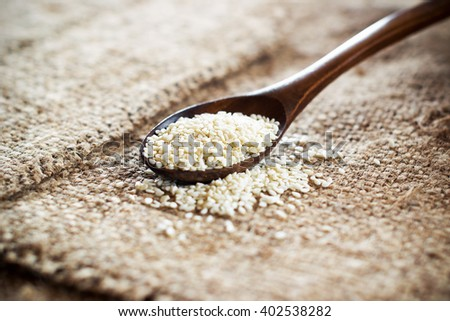 White sesame seeds in a wooden spoon on a linen tablecloth . Shallow DOF - stock photo